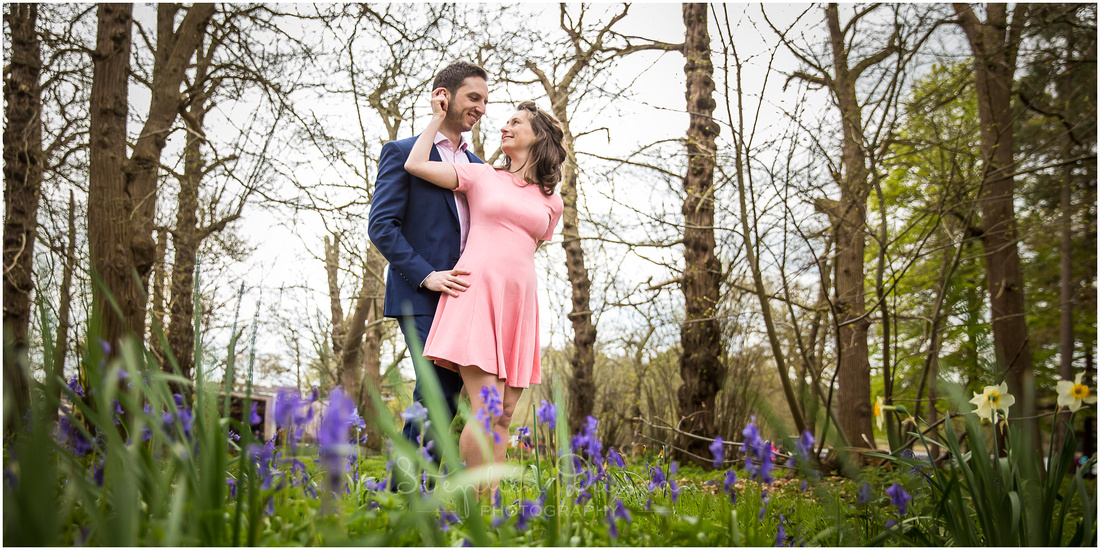 Engagement Shoot couple stood in woodland amongst bluebells in early Spring