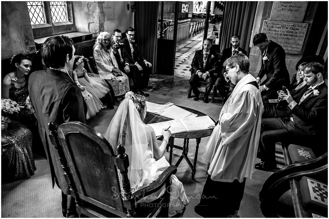 Black and white photograph of bride signing register of marriage
