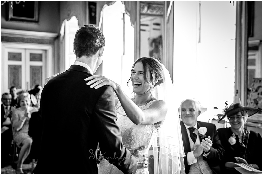 The bride laughs during the wedding ceremony, black and white photo with family members in background