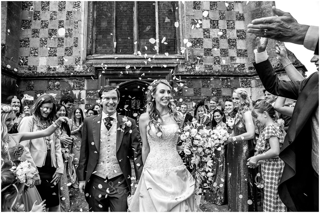 Wedding guests greet the bride and groom with confetti as they leave the church