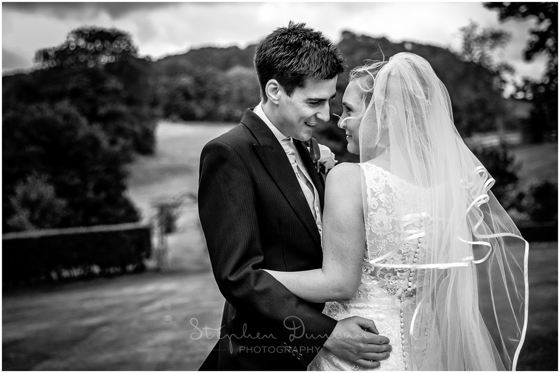 Black and white image of coup;le on hillside at Langrish House Hotel in Hampshire