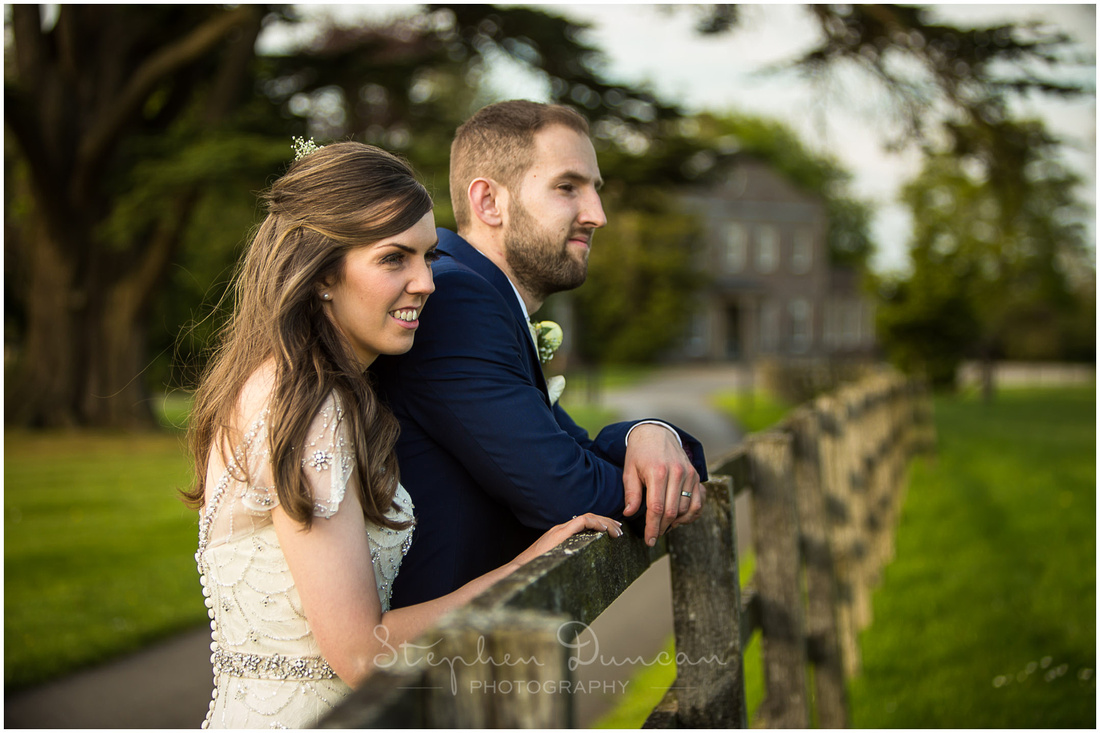 The couple look out across the countryside with the manor house in the background