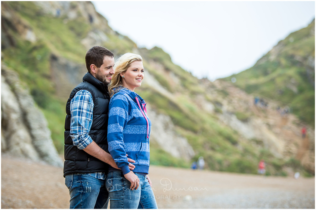 Couple looking out to sea on pebbled beach in Dorset