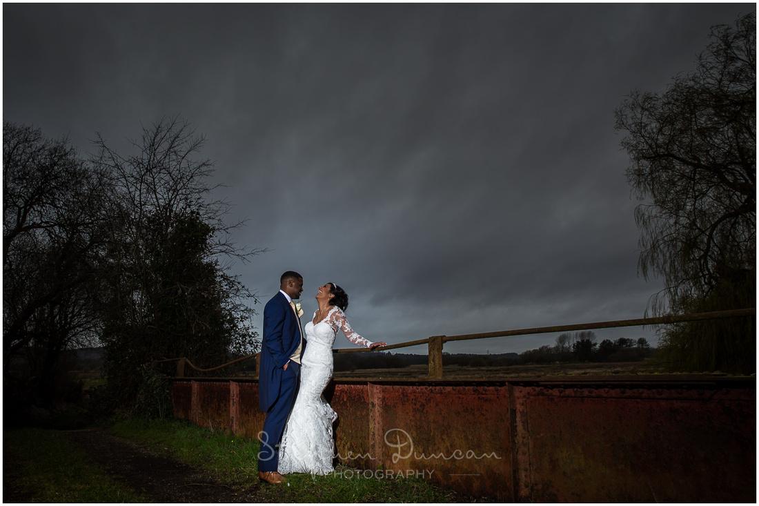 Colour portrait of bride and groom on old rusty bridge at wedding reception venue near Christchurch