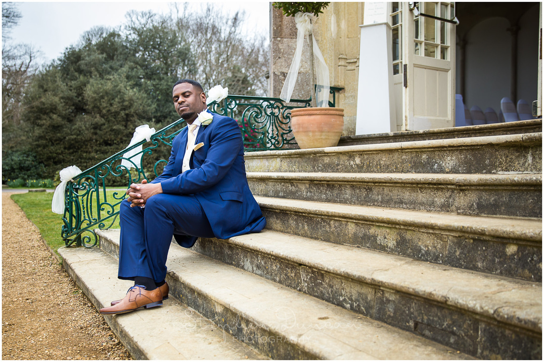 The groom sits on steps outside the ceremony room at Highcliffe Castle in the New Forest