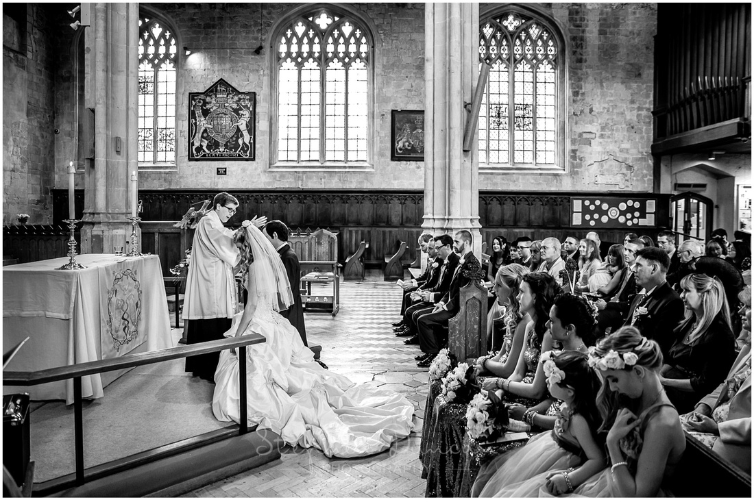 Bride and groom receive the blessing following the wedding ceremony