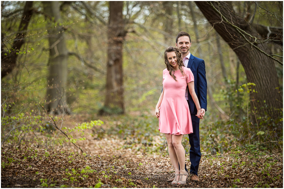 Couple stood alone in woodland in early Spring as green shoots and leaves start to appear on the branches