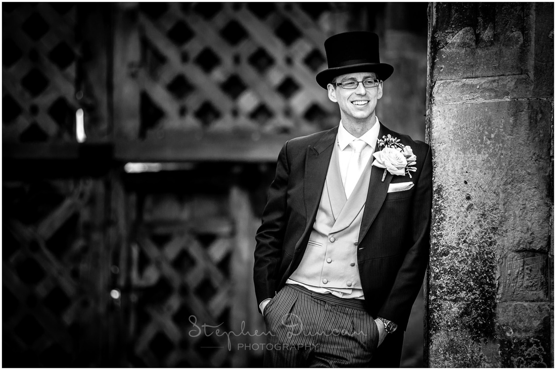 Black and white image using natural light of groom resting against a wall at Titchfield Abbey