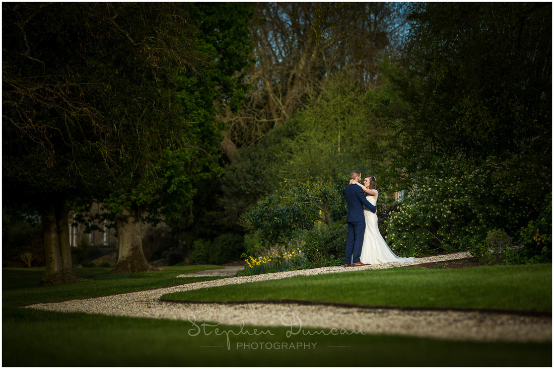 The bride and groom stand alone in the landscaped grounds of the country estate