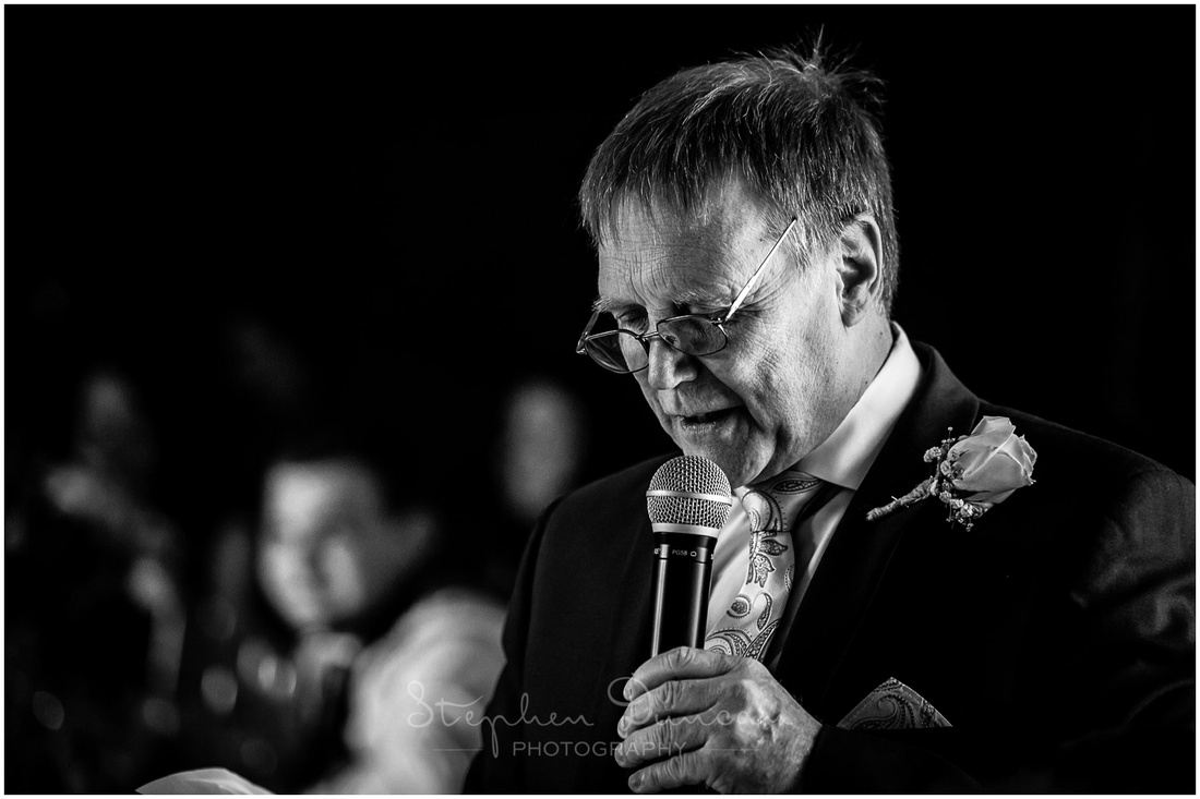 Black and white photograph of bride's father during his speech