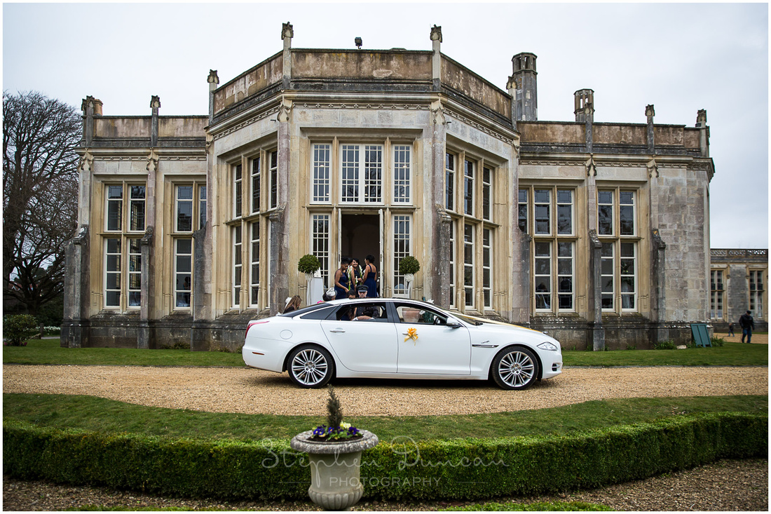 The bride pulls up outside the ceremony room in a white Jaguar