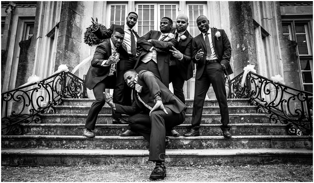 Groom, best man and ushers on steps of wedding venue