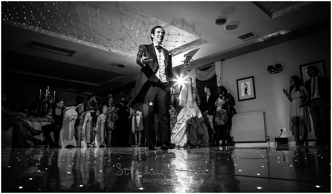 The bride and groom invite other guests to join them on the dancefloor