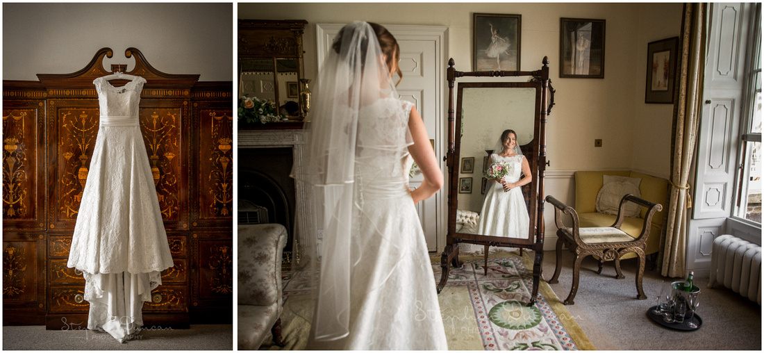 IMage of wedding dress hanging and bride looking at herself in reflection in mirror in bridal suite