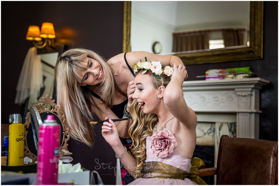 Floral decorations are added to the hair of one of the flower girls
