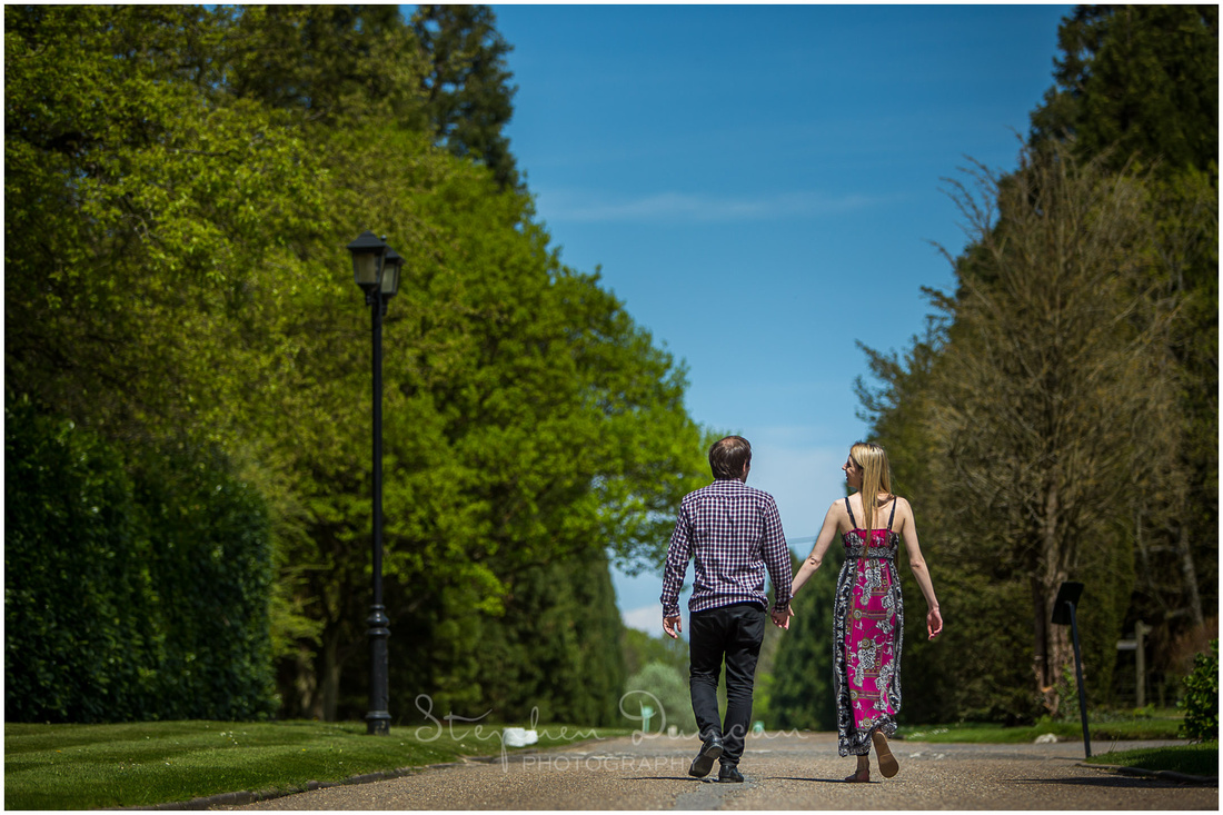 Sunshine colour photo of bride and groom walking along driveway