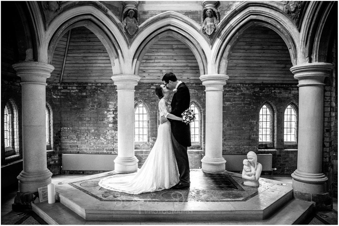 Black and white photo of bride and groom kissing in the attractive chapel to the side of the main church