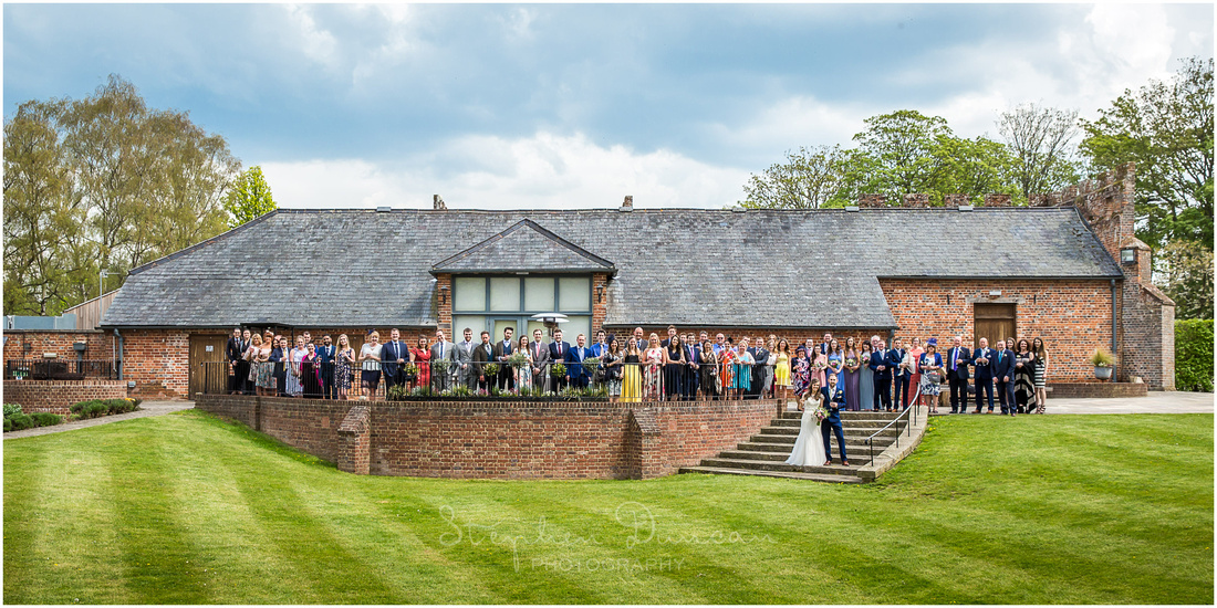 Wedding guests assembled on the terrace outside the barn for the traditional group photo