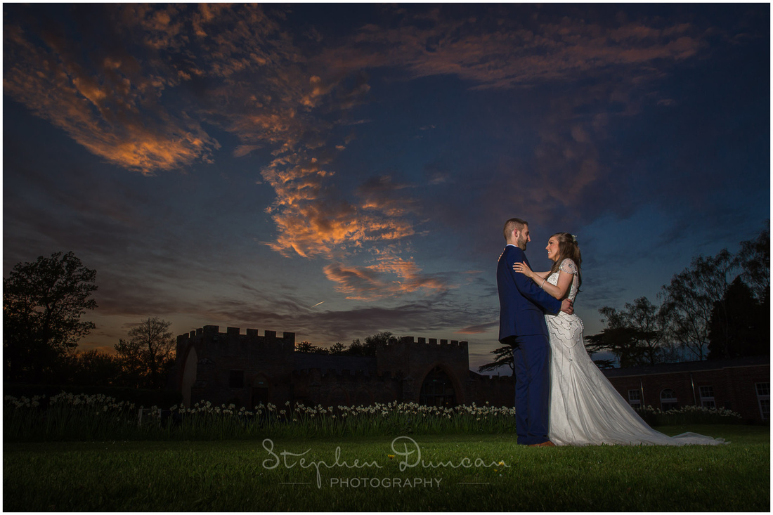 The sun sets behind the turret-like crenellations of the barn reception venue at wasing park