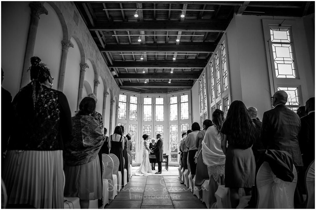 Photograph taken from back of ceremony room with bride and groom in front of large bay window
