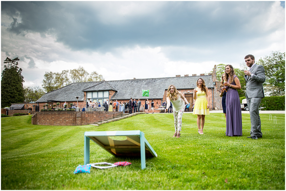 Wedding guests play games on the lawn outside the reception venue