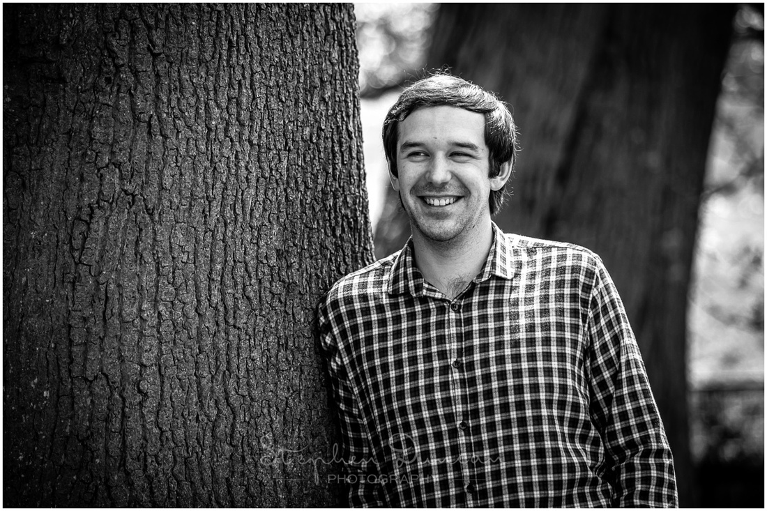 Black and white image of groom leaning against tree in gardens of wedding venue