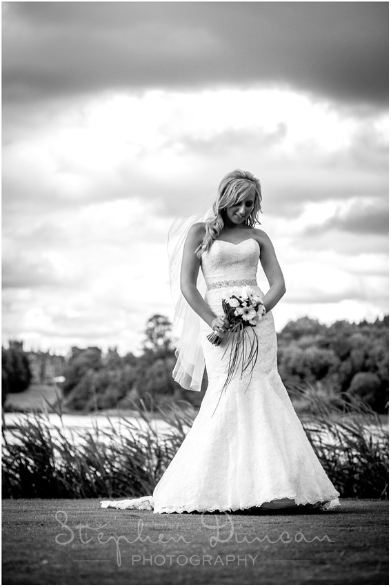 The bride alone by one of the signature lakes of the course