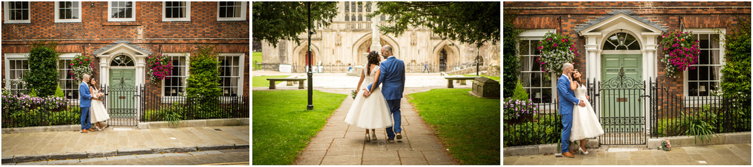 Couple pose outside and old house in the centre of Winchester and walk hand in hand towards the Cathedral