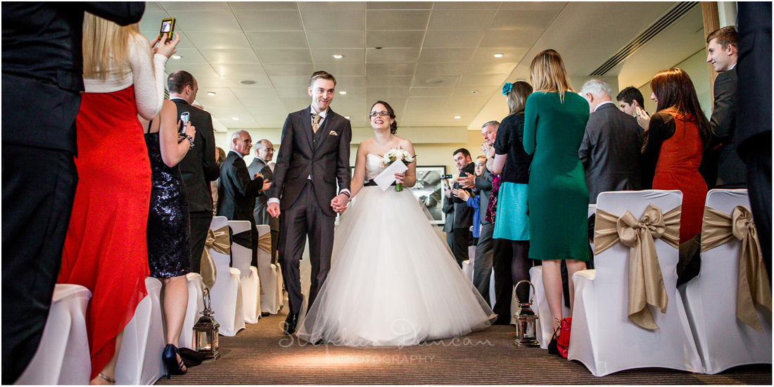 The newly married bride and groom walk down the aisle together