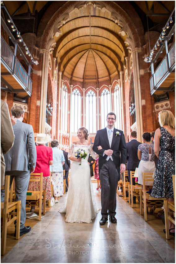 The newly married couple walk arm-in-arm down the aisle