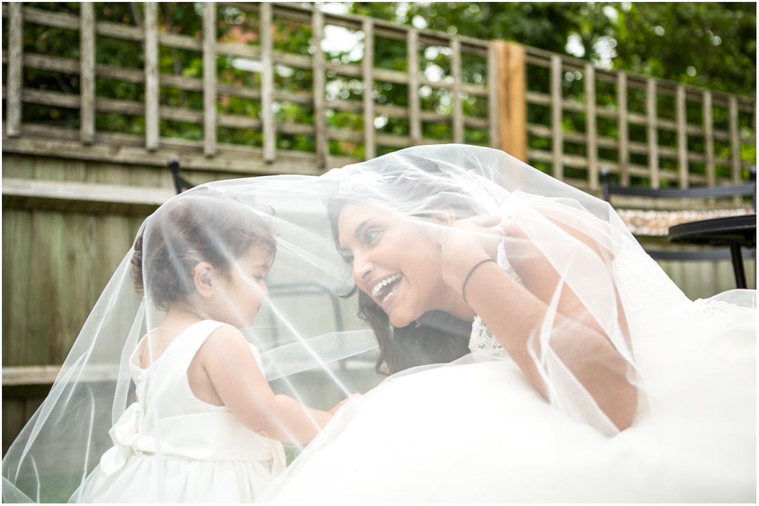 A fun moment as the bride's daughter explores the world underneath ner mum's veil