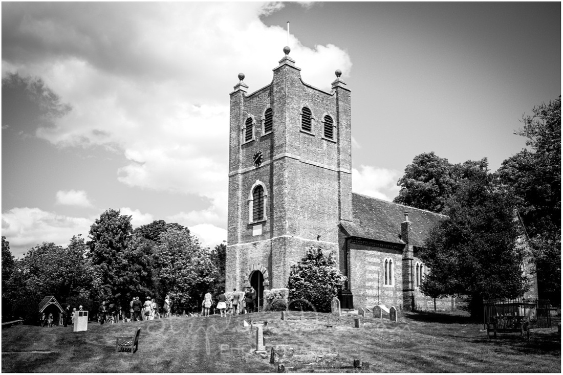 St Mary's church with wedding guests arriving photographed from the west side