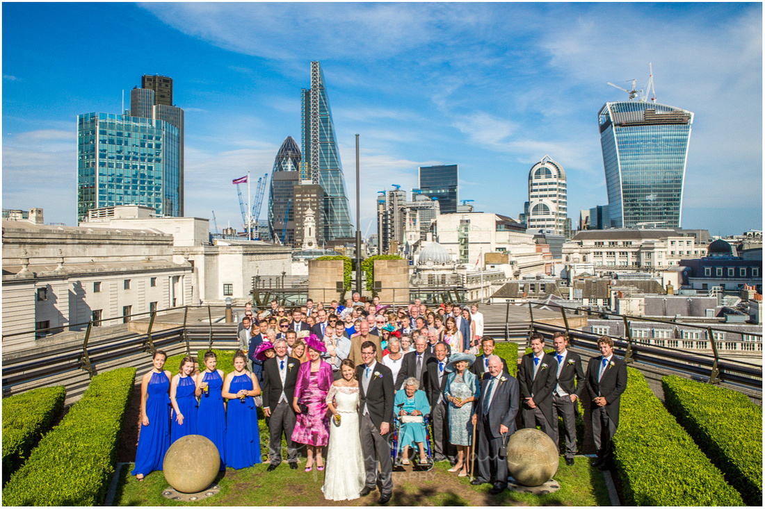 The full wedding party on the roof terrace with the iconic buildings of London's financial district in the background