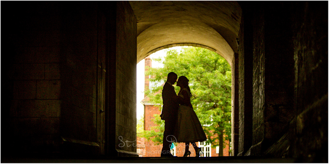 Couple backlit in an archway on the south side of the Cathedral, near the Dean Garnier Garden