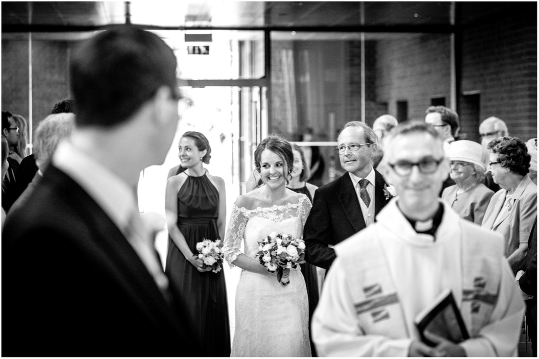 Black and white photo of the bride smiling as she walks down the aisle on her father's arm