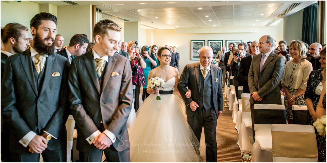 Groom and best man in ceremony room as bride arrives