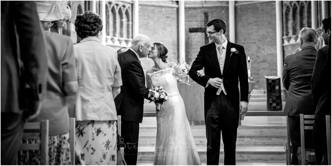 The bride pauses to kiss her grandfather before walking down the aisle with her husband