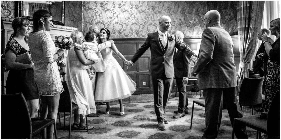 Bride and groom are congratulated by guests as they leave the ceremony room