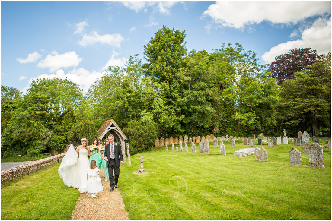 The bride walks to the entrance of the church with her father and flower girl