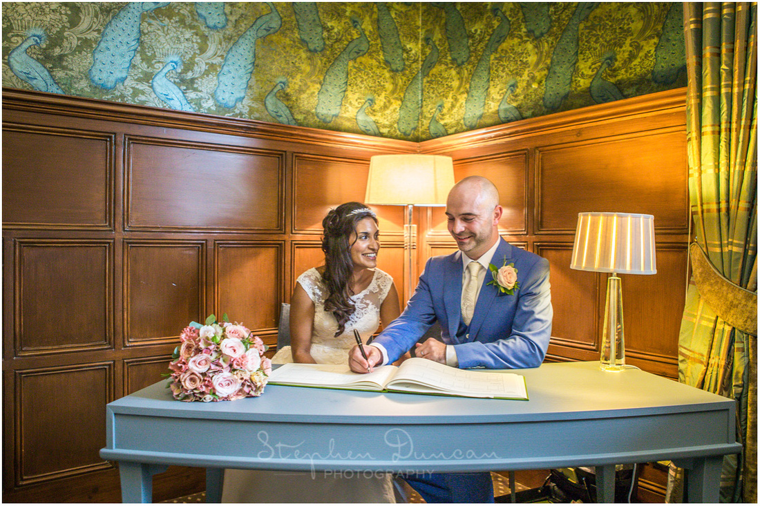 The bride and groom sign the register at a curved table in a corner of the ceremony room