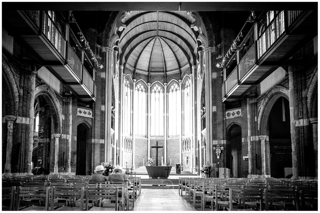 Wide angle black and white photo of interior of all saints church