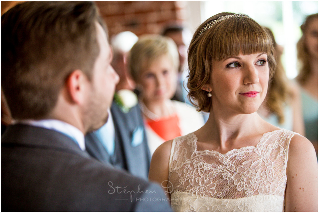 Portrait of bride with guests in the background during the wedding ceremony at Sopley Mill