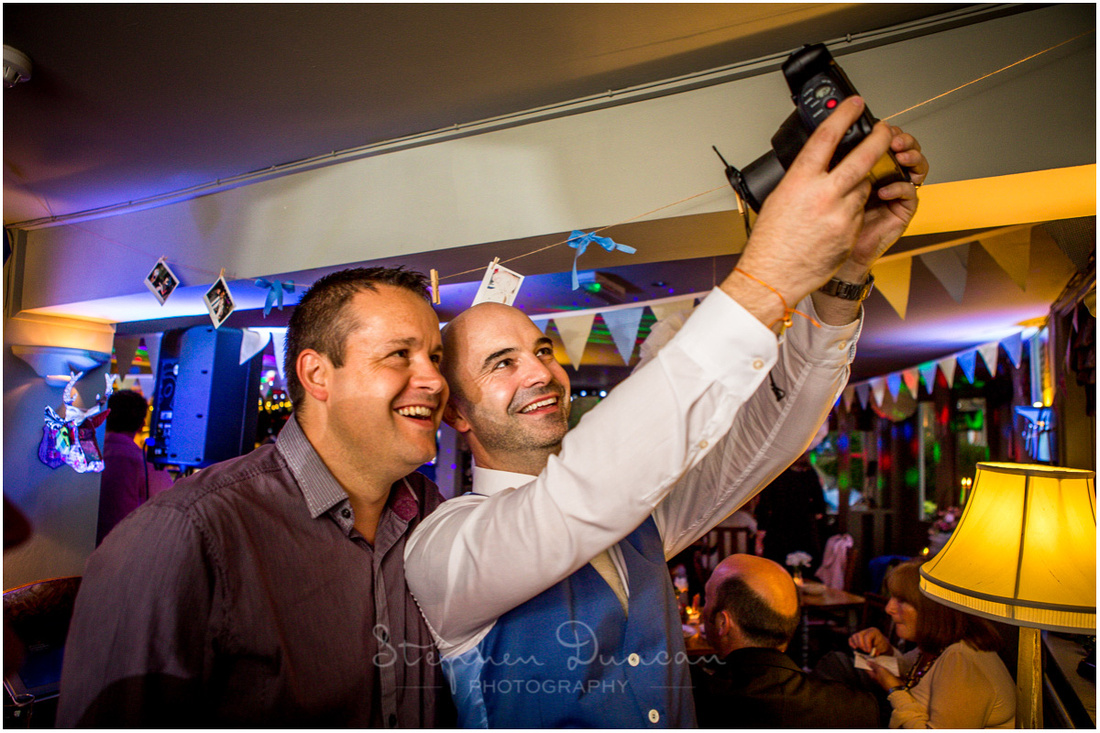 Groom and guest take a selfie with a polaroid camera at wedding reception