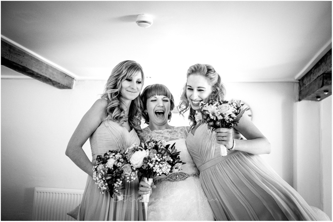 Black and white photo of bride and bridesmaids before ceremony in venue dressing room