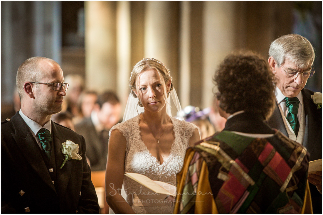 The bride watches on as the vicar leads the wedding ceremony