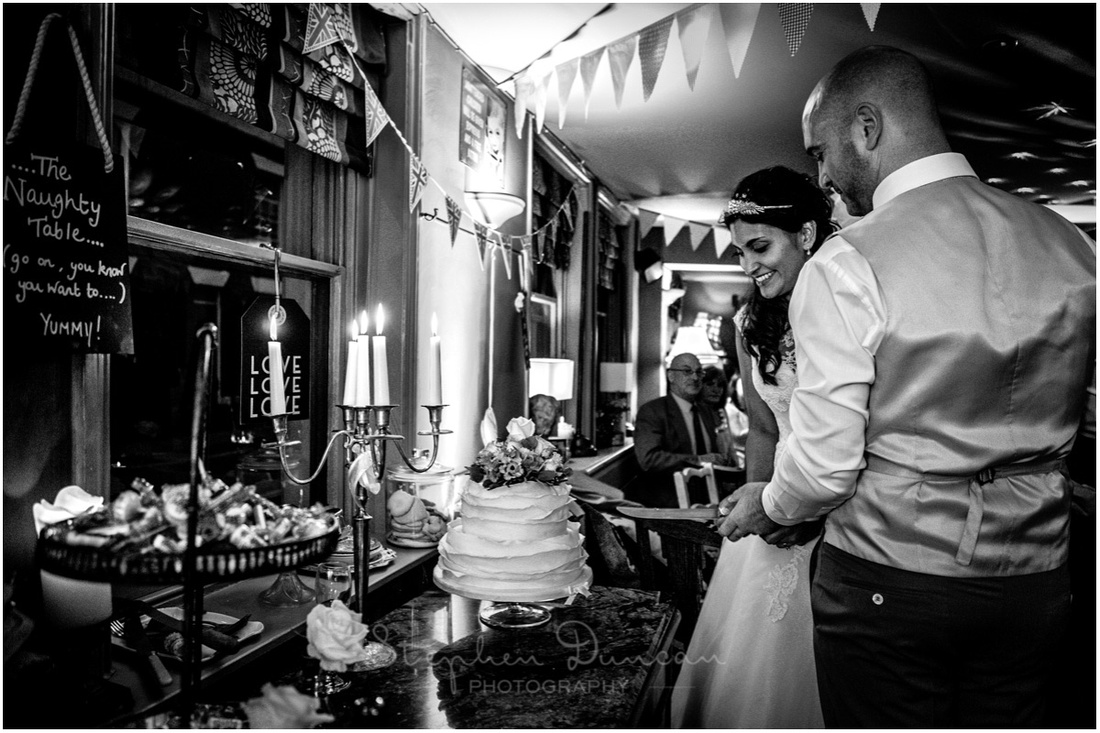 Traditional cutting of the the cake as part of the wedding celebrations at the Corner House in Winchester