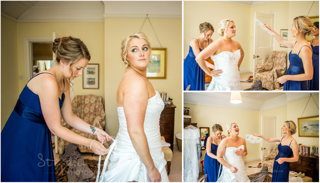 Bridesmaids fan the bride on an extremely hot summers day to keep her cool as the final touches are applied to the dress