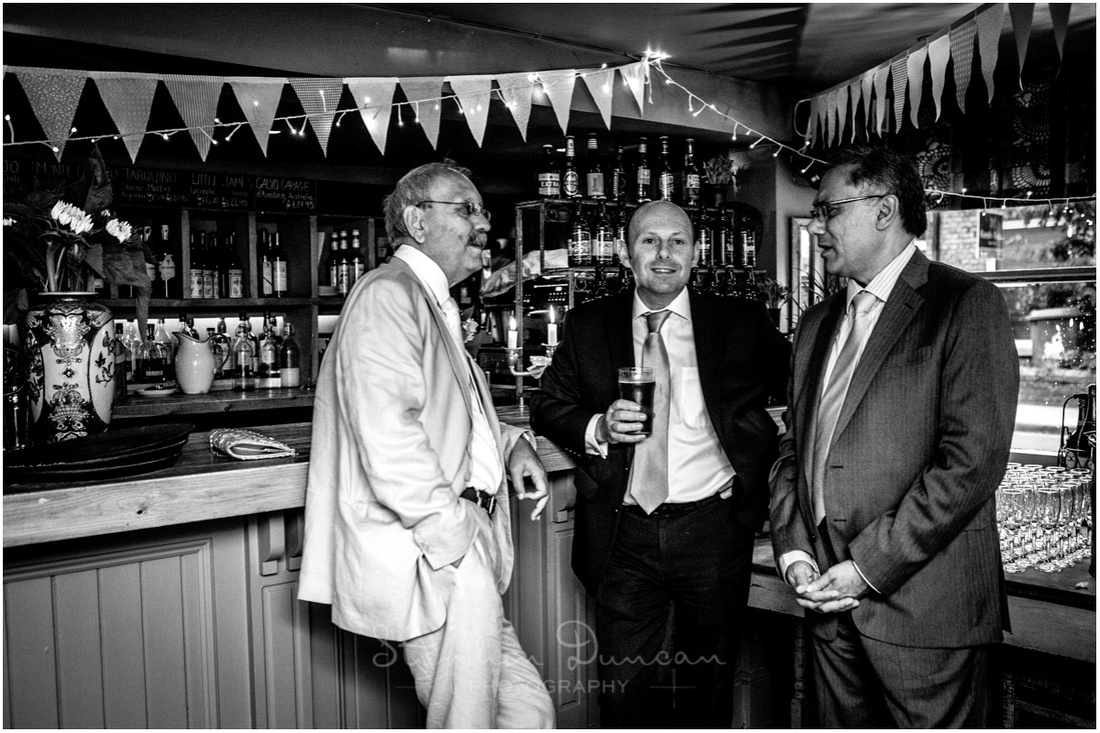Black and white photo of bride's father in conversation with wedding guests at the bar