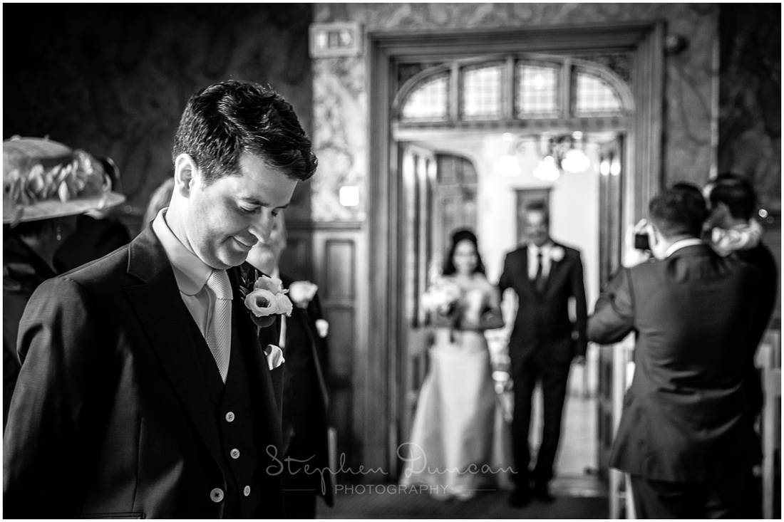 Black and white photo of groom as bride enters the Basing Room in Winchester for wedding ceremony