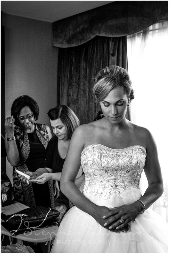 The bride getting into her dress at the Syon Park Hilton Hotel